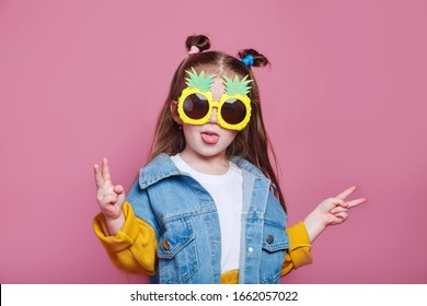 Summer fashion concept. cheerful little girl in big pineapple sunglasses on pink background