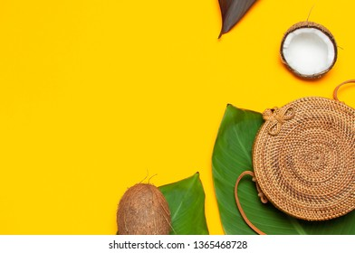 Summer fashion concept. Fashionable handmade natural organic round rattan bag, fresh coconut and tropical leaves on yellow minimalistic background flat lay copy space. Trendy bamboo bag Ecobags Bali.