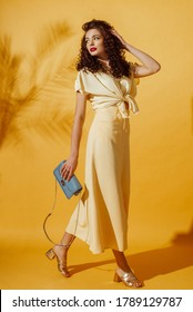 Summer fashion concept: woman wearing monochrome yellow outfit, holding small blue bag, posing in studio on yellow background.