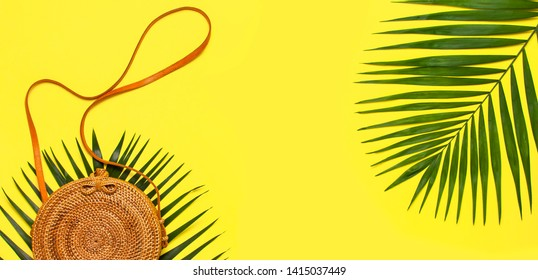 Summer fashion flat lay. Fashionable handmade natural round rattan bag and tropical palm leaves on yellow background. Top view copy space. Trendy bamboo bag Ecobags from Bali. Tropical background