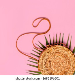 Summer fashion flat lay. Fashionable handmade natural round rattan bag and tropical palm leaves on pink background. Top view copy space. Trendy bamboo bag Ecobags from Bali. Tropical background