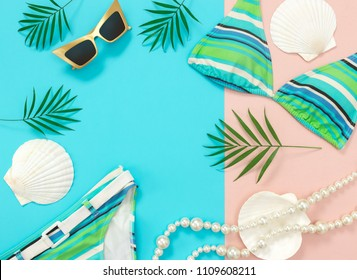 Summer fashion flat lay on blue and pink background. Sunglasses, bikini, pearl necklace, seashells and palm leaves.