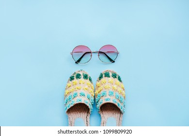 Summer fashion flatlay with gradient round sunglasses and espadrille sandals on the blue background. Perfect beach set for holidays on the sea. Marina style.