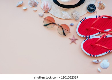 Summer fashion flatlay with gradient round sunglasses, straw hat, flats and red striped bikini top. Decorated with sea shells. Perfect beach set for holidays on the sea. Marina style.