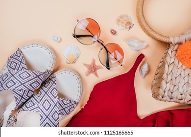 Summer fashion flatlay with gradient round sunglasses, straw bag with pompoms and red swimsuit with frills on beige background. Decorated with sea shells. Perfect beach set for holidays. Marina style.