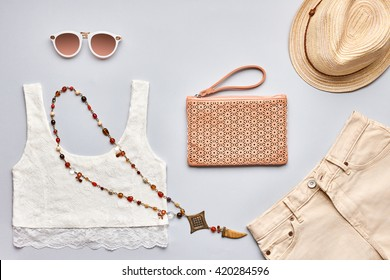 Summer Fashion girl clothes set, accessories. Creative urban hipster pastel colors. Stylish lace top, trendy sunglasses, handbag clutch, necklace, beige hat. Unusual modern outfit