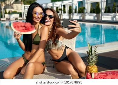 Summer Fashion. Girls Having Fun Taking Photos Near Pool. Sexy Women In Trendy Sunglasses And Fashionable Bikini Swimwear Making Selfies And Enjoying Luxury Vacation At Resort Hotel. High Resolution.