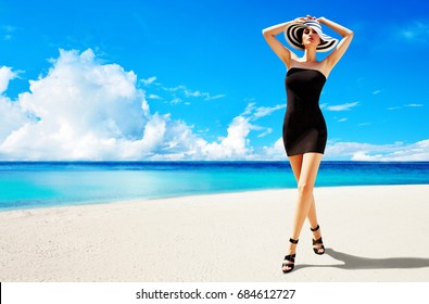 Summer fashion image. Beautiful woman with black dress, heels shoes, and hat walking on the sunny beach.