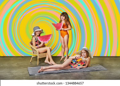 Summer fashion kids. Group little girl in swimsuits for sunbathing.Three bright children models,color rainbow background,studio.Happy girlfriend holding watermelon art. Concept vacation,heat, travel.