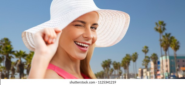summer, fashion and people concept - portrait of beautiful smiling woman in sun hat over venice beach background in california