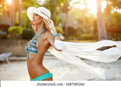 Summer fashion portrait of beautiful tanned woman relaxing on a sunset beach