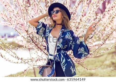00f411907ed3 Summer fashion portrait of pretty blonde woman posing on amazing blooming  tree background .Wearing sunglasses