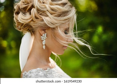 Summer fashion portrait of a stunning blonde woman, with stylish hairstyle and perfect makeup, wearing a lace dress and expensive earrings. Young bride enjoying summertime. Romantic mood