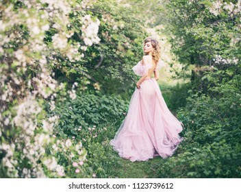 Summer fashion portrait of stunning woman walking in the blooming park. Wearing long boudoir dress. Ball gown. Romantic mood. Enjoying nature of the flowering apple tree on a sunny day. Spring time