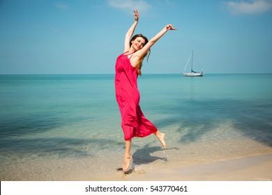Summer fashion portrait of stunning woman soaring on the tropical beach. Jumping and enjoying life in paradise. Sea background. In the distance a boat in the sea. Wearing bright long red dress