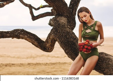 Summer fashion portrait of stunning women with slim sexy body on the beach. Holding in her hands bunches of rambutan. Enjoying life in paradise. Wearing stylish high waist bikini. Tropical island