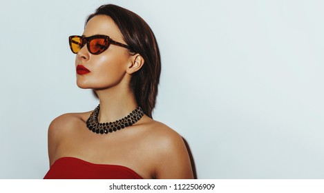 Summer Fashion portrait. Youg sexy tanned woman in sunglasses posing. Shining healty skin and highlighter make up. Banner with copy space