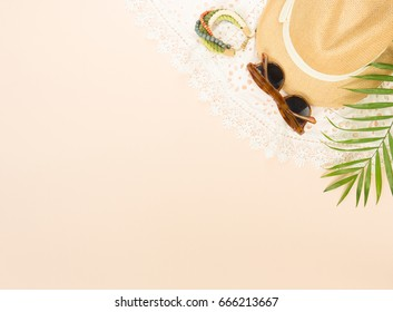 Summer fashion, summer stuff on cream background. White lace dress, retro sunglasses, wood bracelet and straw hat. Flat lay, top view.