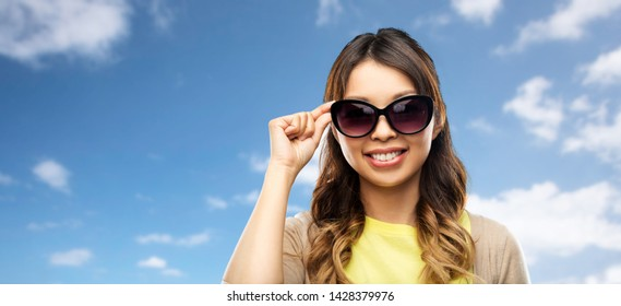 summer fashion, style and eyewear concept - happy smiling young asian woman in sunglasses over blue sky and clouds background
