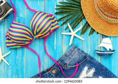 Summer Fashion woman big hat and accessories, vintage camera go to travel in vacations the beach. Tropical sea.Unusual top view and copy space blue background. Summer and Holiday Concept.