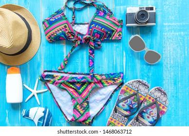 Summer Fashion woman swimsuit Bikini, camera, starfish, sunblock, sun glasses, hat. Travel in the holiday wood blue background.  Summer Concept.