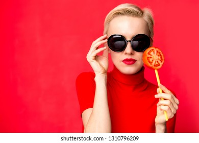 Summer fashion woman wearing sunlglasses and holding tomato lollipop against red wall. Beauty, food, diet concept