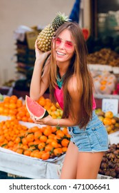 Summer fashionable girl is posing with pineapples and slice of watermelon on tropical fruits background.