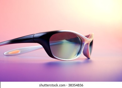 Summer - fashionable sunglasses on color background under sun light