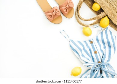 Summer female fashion stylish composition. Dress, slippers, straw, tulip flower, lemons on white background. Flat lay, top view clothes and accessories collage.