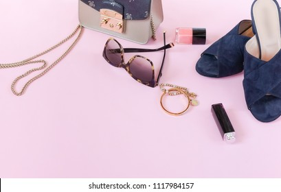 Summer female fashion stylish lyxury clothes composition. Sandals, bag, sunglasses, make up products, accesories on pale pink background. Flat lay, top view collage.copy space