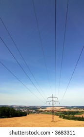 Summer field with transmission poles and sky