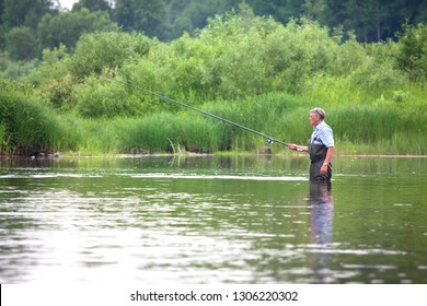 Summer fishing on the lake.  A man pulls a fish out of the river, in the hands of a fishing rod and net.  Beautiful summer landscape. A lot of green vegetation, reflected in the water. Summer season.