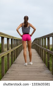Summer fitness lifestyle motivation. Back view of young sporty woman taking an outdoor running workout rest.