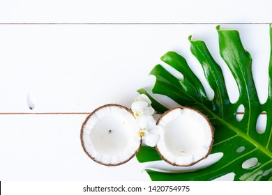 Summer flat lay scene with green tropical leaves and cocnut fruit on white wooden background with copy space