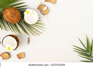 Summer flat lay scene with palm leaves and flowers with coconut fruits on wooden background with copy space