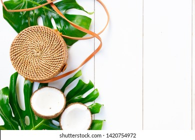 Summer flat lay summer scenery, bag, green leaves on white wooden background with copy space