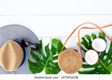 Summer flat lay scenery, bag, leaves and cocnut on white background with copy space