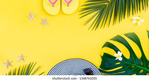Summer flat lay scenery on yellow background with palm leaf and flip flops, banner with copy space