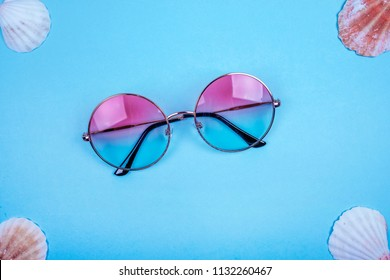 Summer flatlay with round gradient sunglasses and sea shells on the bright blue backfround.