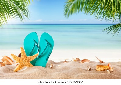 Summer flipflop on sandy beach, blur sea on background. Summer exotic relaxation concept