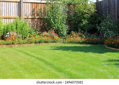 Summer Flower Boarder Surrounding A Grass Lawn In An Home Garden.