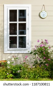 Summer flowers against a wooden summhouse building window in the garden