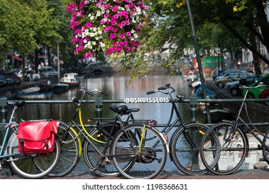 Summer flowers and bicycles on the canal at Bushuissluis bridge translated as bus garage lock, Amsterdam, Netherlands