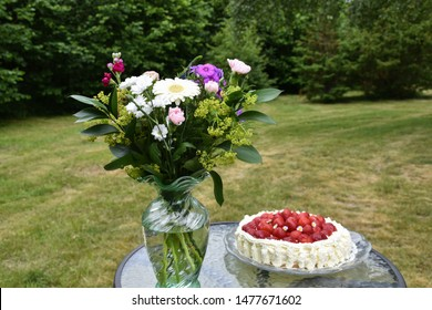 Summer flowers and a delicious strawberry cake on a table  in a garden