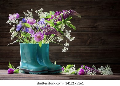 summer flowers in rubber boots on old dark wooden background