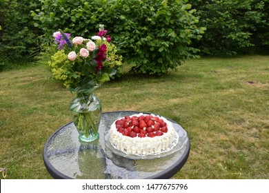 Summer flowers and strawberry cake on a table in a green garden