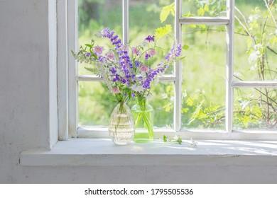 summer flowers in vase on windowsill in sunlight - Shutterstock ID 1795505536