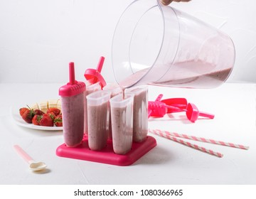 Summer food: cooking home-made fruit ice. Filling the prepared mass in ice cream molds.