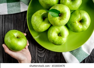 summer food with green apples in plate on dark background top view