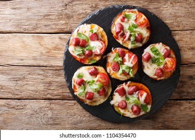 Summer food: hot eggplant with cheese, tomatoes, sausage and sauce close up on a slate board on the table. Horizontal top view from above